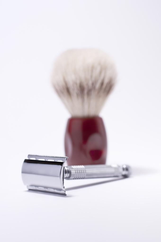 Maquinilla de afeitar con borcha en fondo blanco