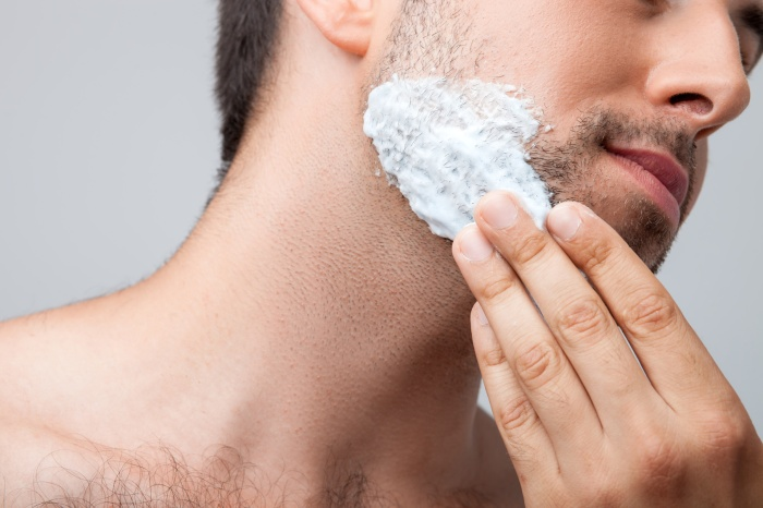 Attractive young guy is shaving his beard
