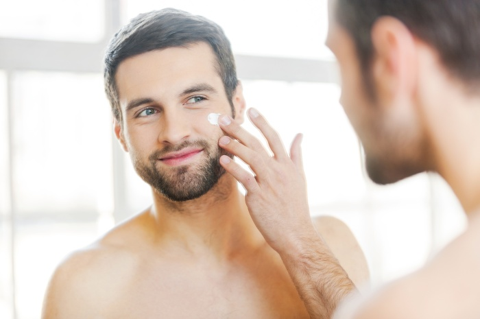 Skin care. Handsome young shirtless man applying cream at his face and looking at himself with smile while standing in front of the mirror