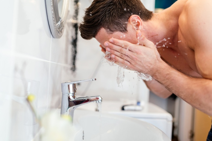 Handsome man washing face in bathroom in morning