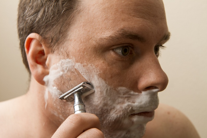 Using an old fasion safety razor man is shaving his face